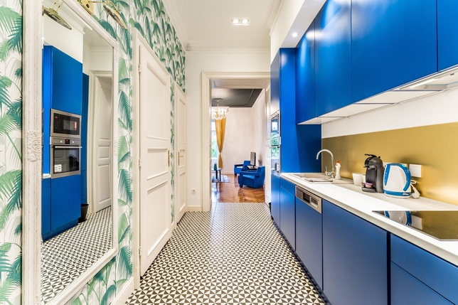 bold coloured cabinets and patterned wallpaper in a narrow, urban kitchen
