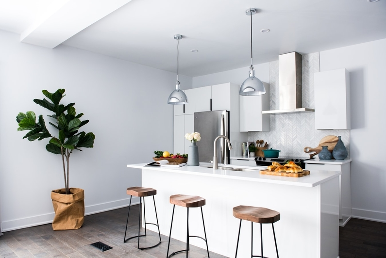 silver metallic hanging lights over kitchen island, wooden stools and house plant