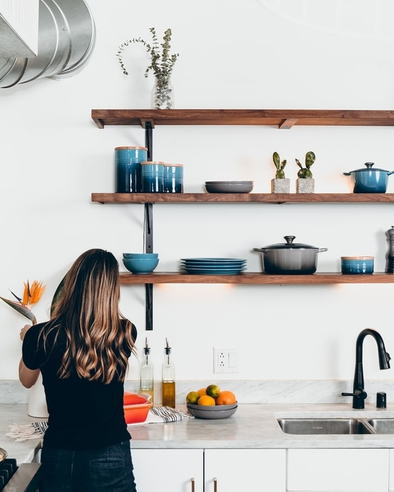 open shelving displaying plants and coloured storage jars and utensils