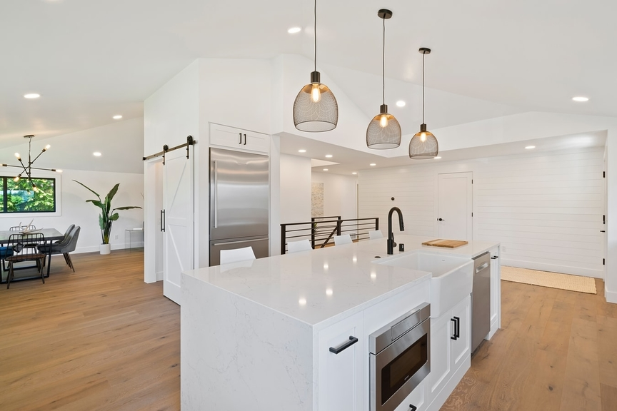white and wood open-plan kitchen, pendant lighting above kitchen island