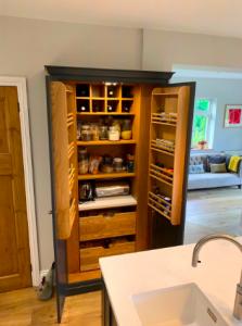 bespoke storage for wine and herbs inside kitchen cupboard