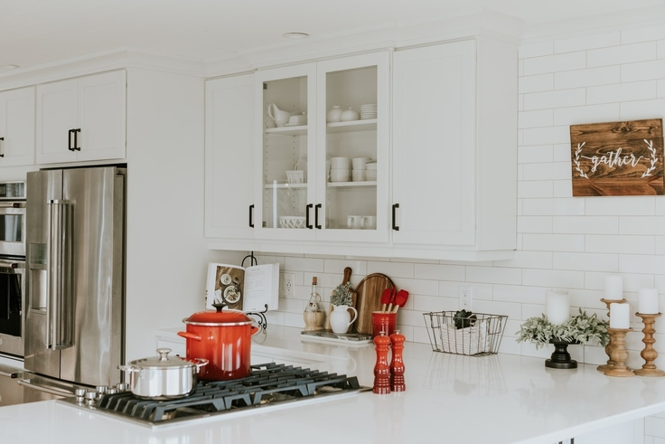 all white kitchen with glass-fronted shaker style cabinets