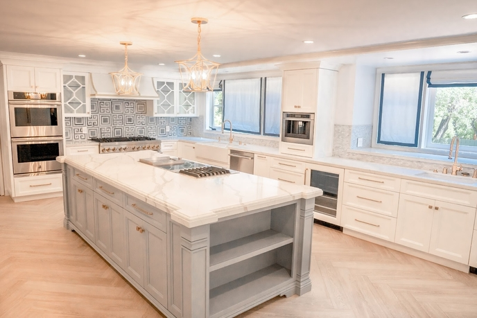 grey and white kitchen with marble topped island and shaker style cabinets