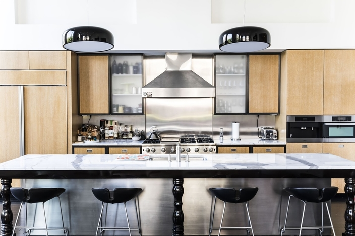 modern black, metal and pine kitchen with island and some frosted glass-fronted cabinets
