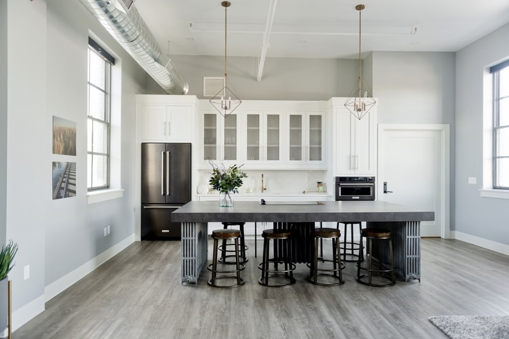white and black kitchen with large island and glass-fronted cabinets